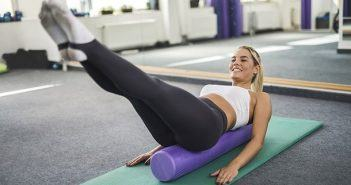 Young happy woman doing balance exercises on Pilates class.